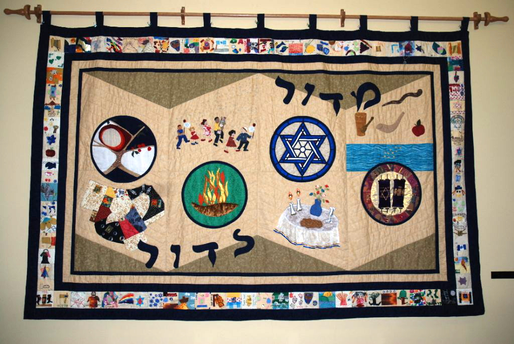 This quilt was crafted completely by congregants for the 40th anniversary of Temple Israel which was in 2006. It took a year to produce, and is hand quilted by many hands! The background is to look like an open Torah scroll, the colours are taken from the Wailing Wall in Israel